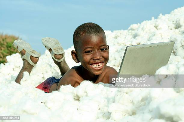 a boy enjoying in a pile of cotton with a laptop - mali photos et images de collection