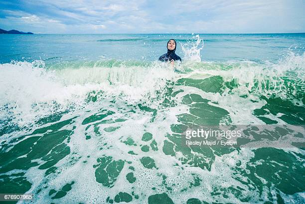 boy enjoying in sea against sky - kuantan stock pictures, royalty-free photos & images