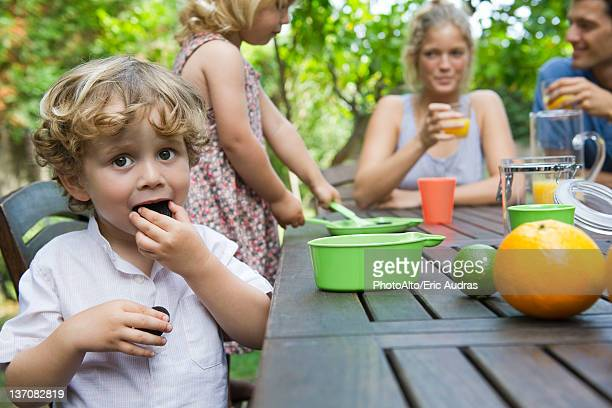 Boy enjoying outdoor snack with his family