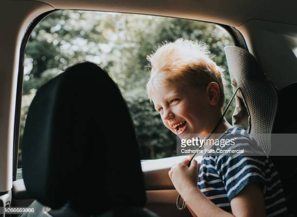 boy enjoying the wind blowing through his hair in the back seat of a car - travel destinations stock pictures, royalty-free photos & images