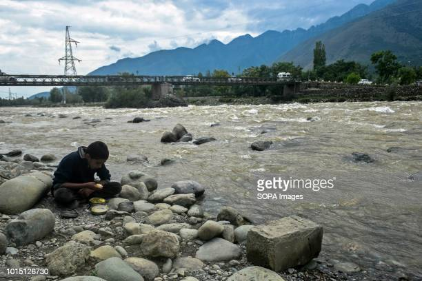 A boy enjoys a meas near the river on the outskirts of Srinagar Indian administered Kashmir Kashmir is the northernmost geographical region of the...