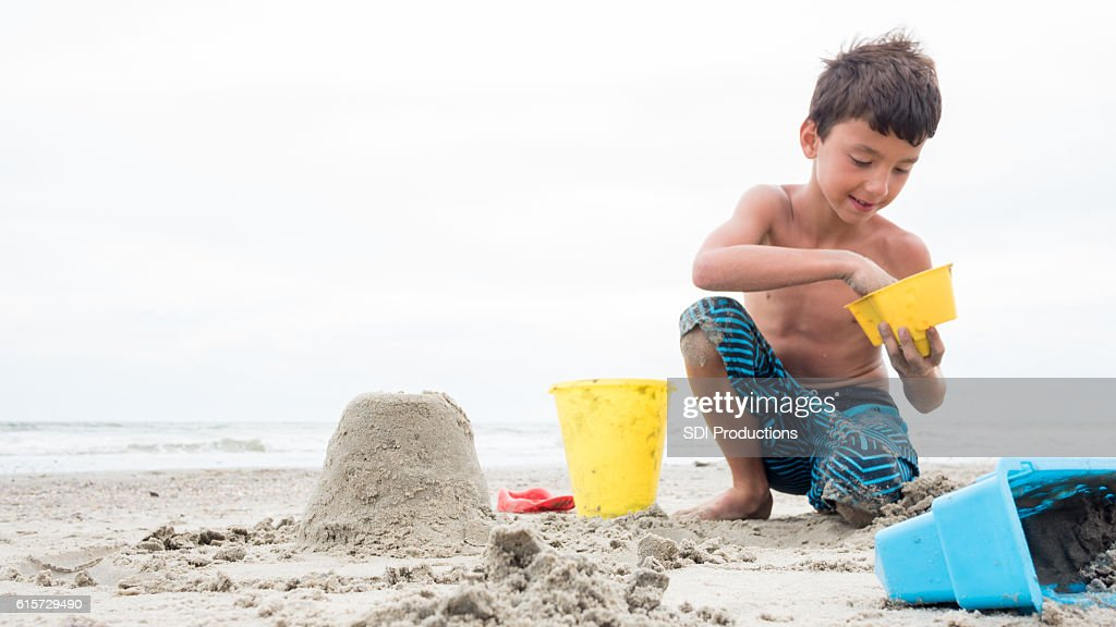 Boy enjoys building a castle in the sand : Stock Photo