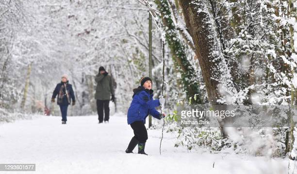 Boy enjoys playing in the snow on December 29, 2020 in Newcastle-Under-Lyme, England. Heavy snow fall has covered the West Midlands as the Met Office...