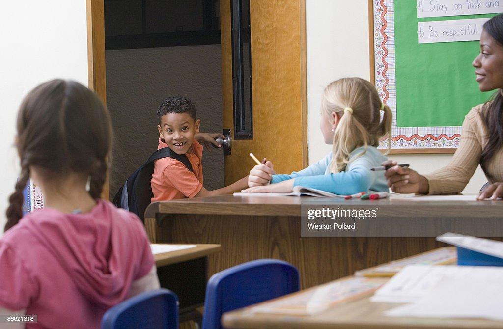 Boy entering classroom late : Stock Photo