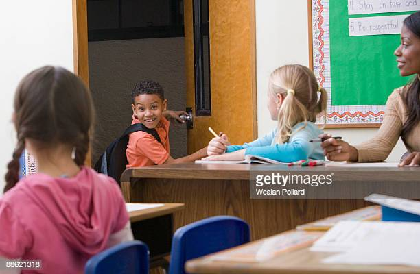 Boy entering classroom late