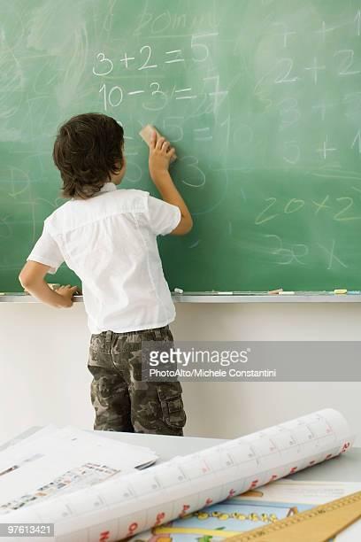 Boy erasing blackboard, rear view