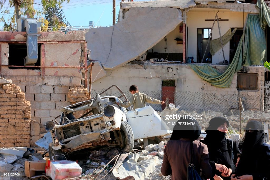 A boy examines a damaged vehicle oustide a Syrian-government-sponsored shopping festival in the Eastern Ghouta town of Douma, on the eastern outskirts of the capital Damascus, on May 13, 2018.