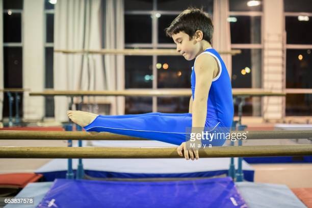 Boy exercising on parallel bars.