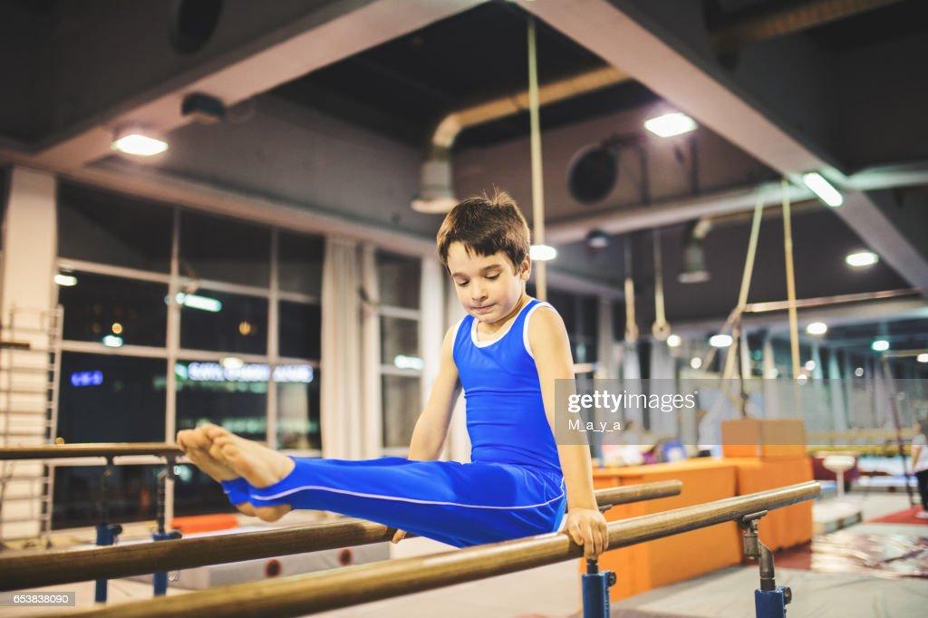 Boy exercising on parallel bars. : Stock Photo