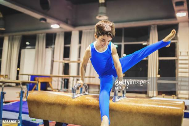 Boy exercising on pommel horse.