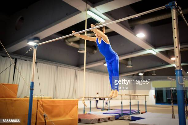 boy exercising on uneven parallel bars - horizontal bars stock pictures, royalty-free photos & images