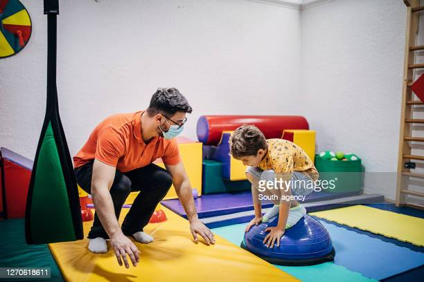jongen die met fysiotherapeut in sensorische ruimte uitoefent - match sport stockfoto's en -beelden