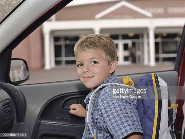 Boy (6-8) exiting car outside school, smiling, portrait