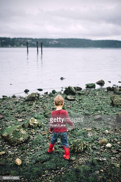 Boy Exploring Rocky Beach