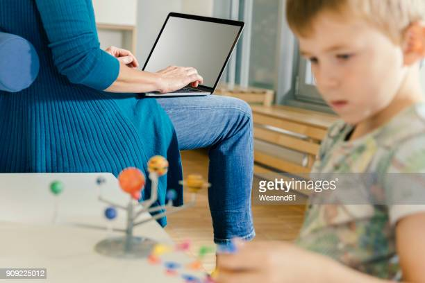 Boy exploring solar system model with woman with laptop in kindergarten