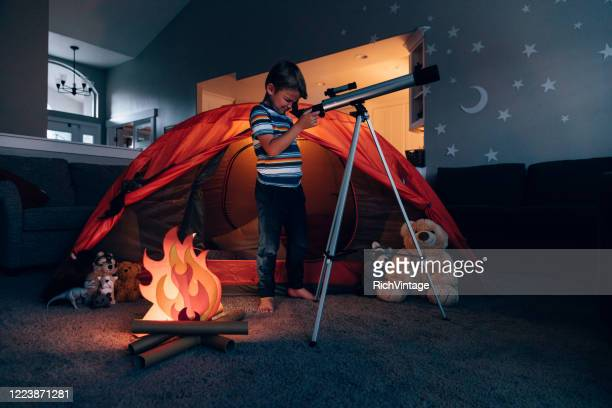 boy exploring with telescope indoors - imagination stock pictures, royalty-free photos & images
