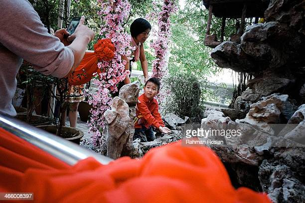 A boy extends his arm for a blessing infront of a sacred fountain in Tien Hou Temple as Malaysian celebrate Chinese New Year on January 31 2014 in...