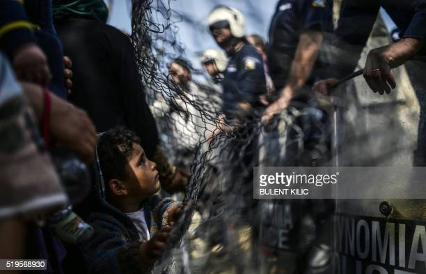 TOPSHOT A boy faces riot police forces during a protest held by migrants and refugees to call for the reopening of the borders at their makeshift...