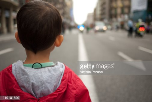 Boy Facing Street With His Back Turned To Camera Stock
