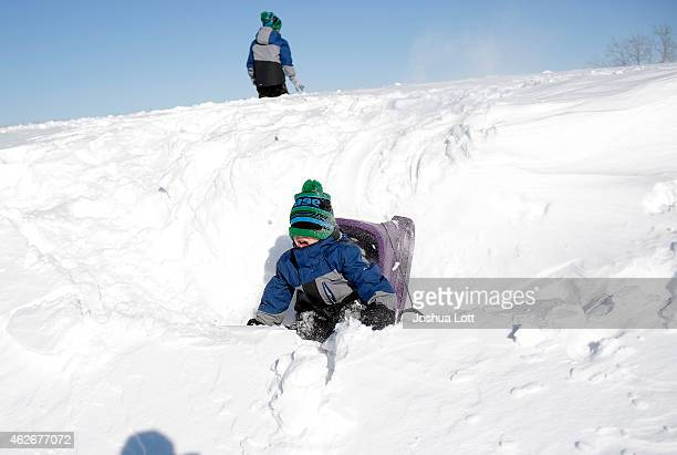 A boy fall off his sled as he plays in the snow February 2 2015 in Detroit Michigan Detroit received over a foot of snow during a storm that has...