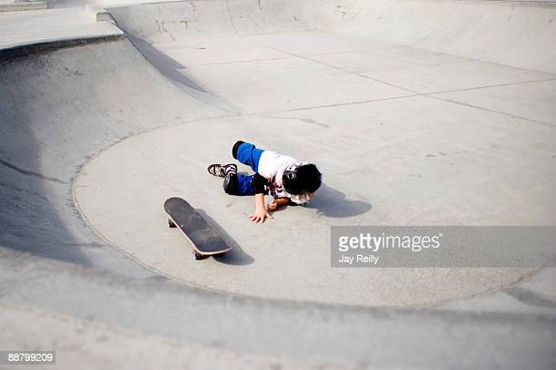 Boy falling from skateboard in skate park