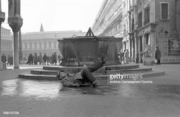 A boy falls on the ice in St Mark's Square during a cold wave in 1963 Venice Italy