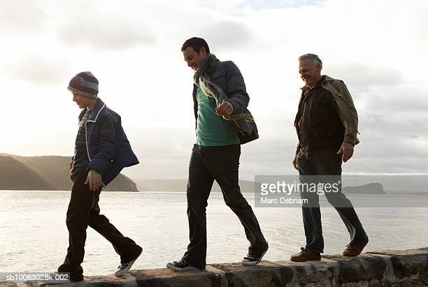 Boy (10-11), father and grandfather walking on wall at edge of lake, side view