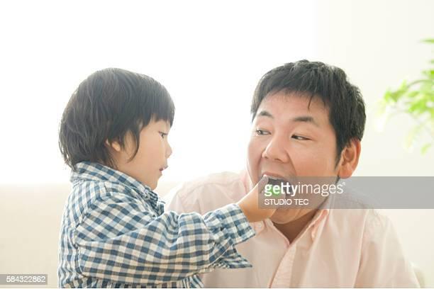 Boy feeding cake to his father
