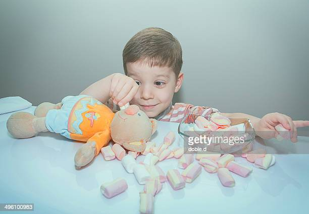 Boy feeding his stuffed toy with marshmallows