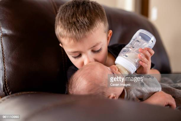 boy feeding milk to brother from baby bottle while kissing him at home - brother stock pictures, royalty-free photos & images