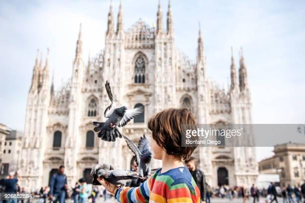 boy feeding pigeons in milan cathedral square, milan, lombardy, italy - piazza del duomo milano foto e immagini stock