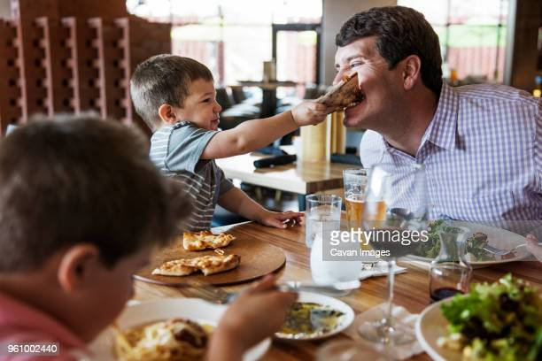 boy feeding pizza to father in restaurant - foco seletivo - fotografias e filmes do acervo