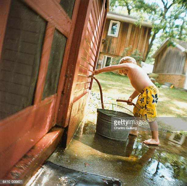 Boy Filling Bucket With Hose
