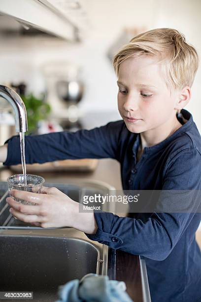 Boy filling water in glass from faucet in kitchen