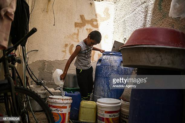 Boy fills a bucket with water brought by a water truck in Gaza City, Gaza on September 9, 2015. At least 120,000 Palestinians face water crisis just...