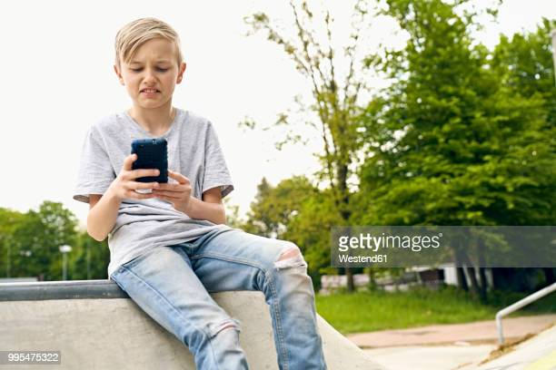 boy finding something disgusting on smartphone - ugly boys photos stock photos and pictures