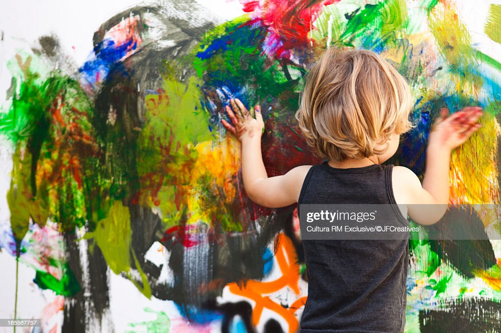 Boy finger painting on large canvas : Stock Photo