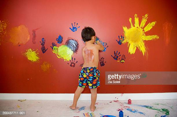 Boy (3-5) fingerpainting on red wall, rear view