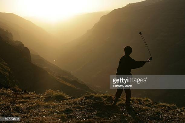 Boy fires slingshot at sunset, Simien Mountains