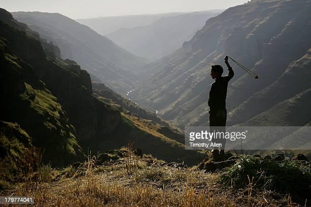 Boy fires slingshot, Simien Mountains