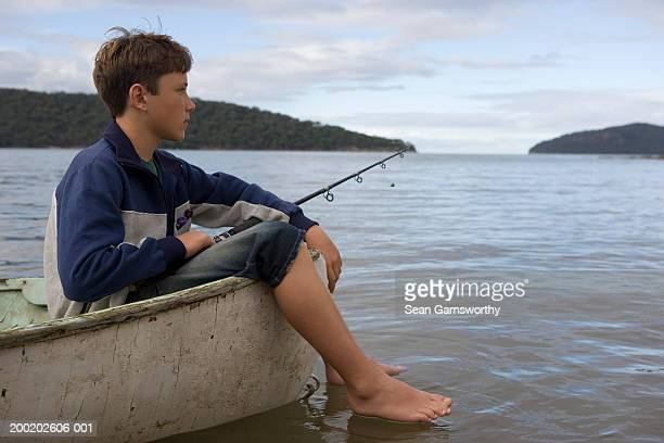 Boy (12-14) fishing from boat, feet hanging over side