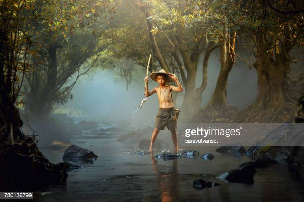 Boy fishing in river, Thailand