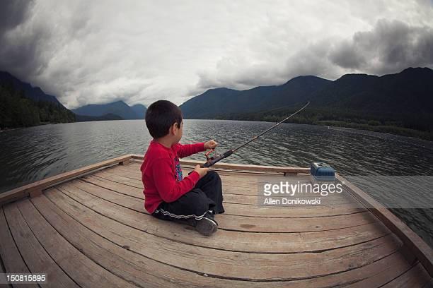 Boy fishing on boat dock at lake