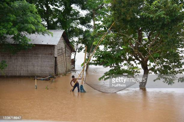 A boy fishing on flood water near his submerged house at Raja Ali village near Kampur in Nagaon in the northeastern state of Assam Indiaon Sept 262020