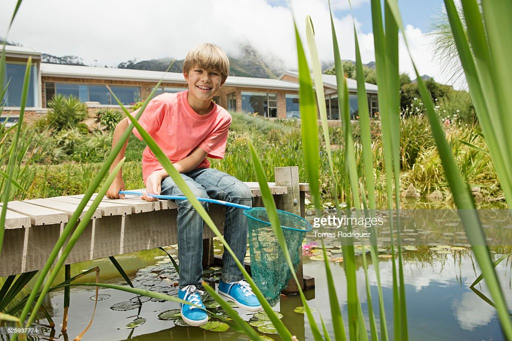 Boy (6-7) fishing on pier : Stock Photo