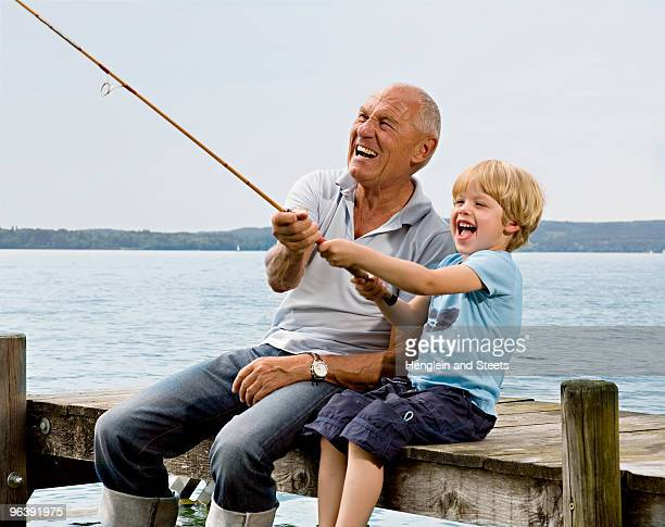 boy fishing with grandfather at lake