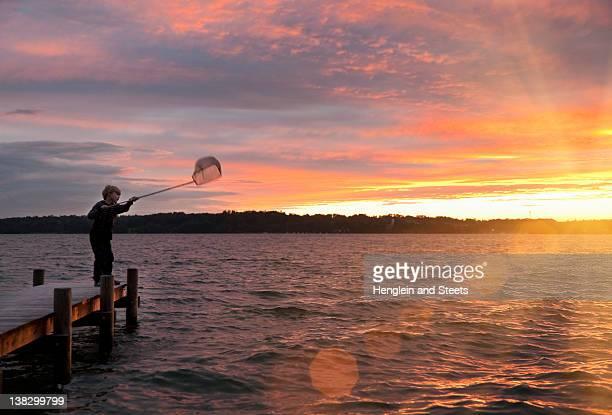 garçon avec filet de pêche sur le lac - starnberg photos et images de collection