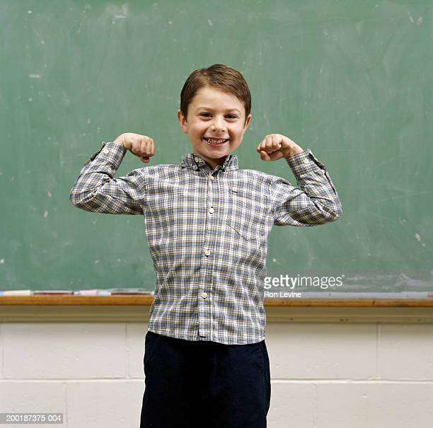 boy (4-6) flexing biceps in front of blackboard, portrait - schulkind nur jungen stock-fotos und bilder