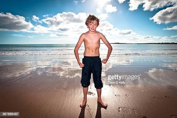 boy flexing his muscles on a beach - muscle men at beach stock photos and pictures
