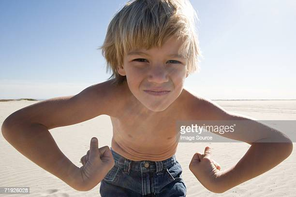 Boy flexing muscles on beach